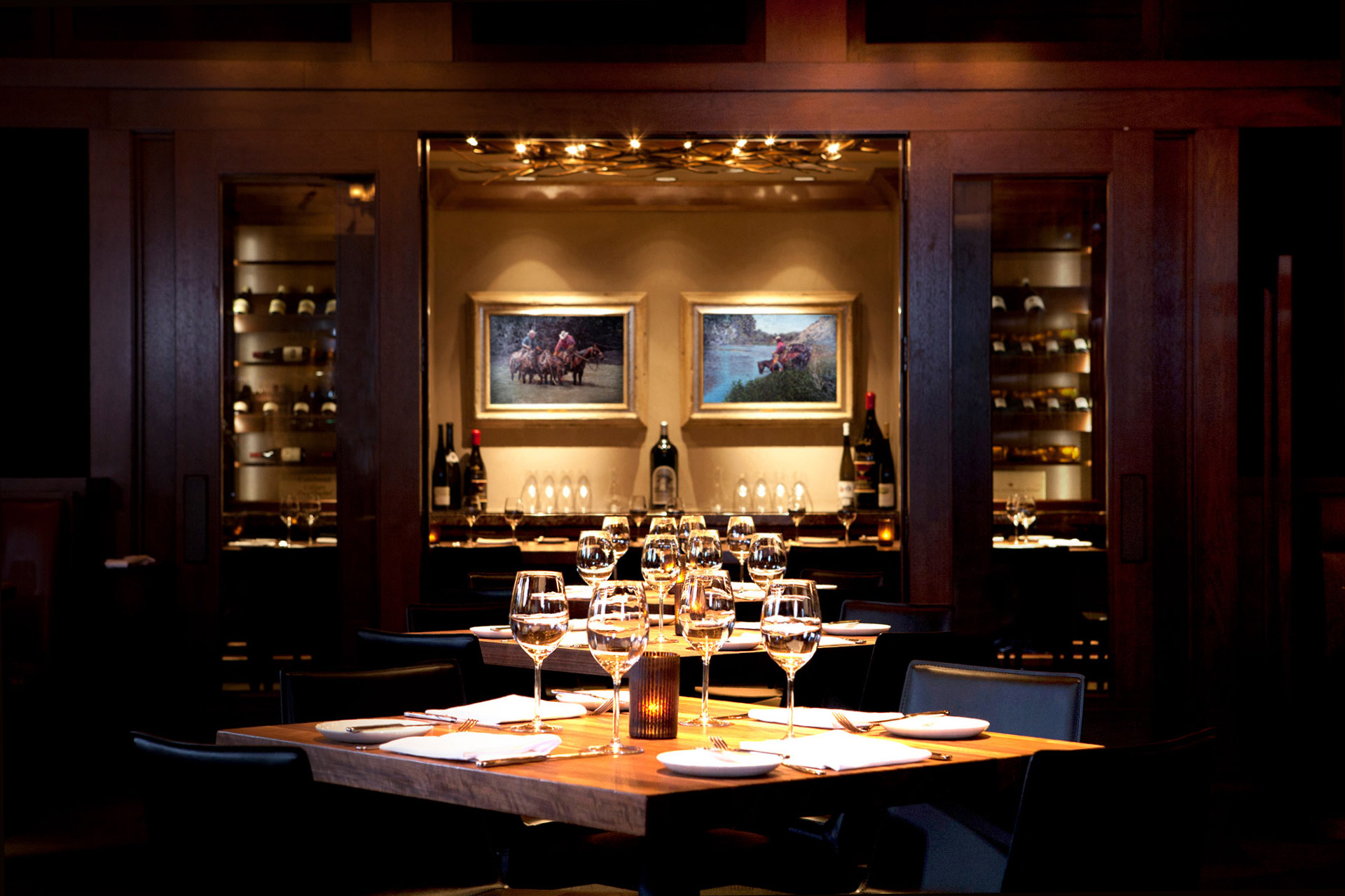 Wood-paneled dining room and gleaming table with glasses of wine selected by Executive Chef and Master Sommelier, Michael Rossi.