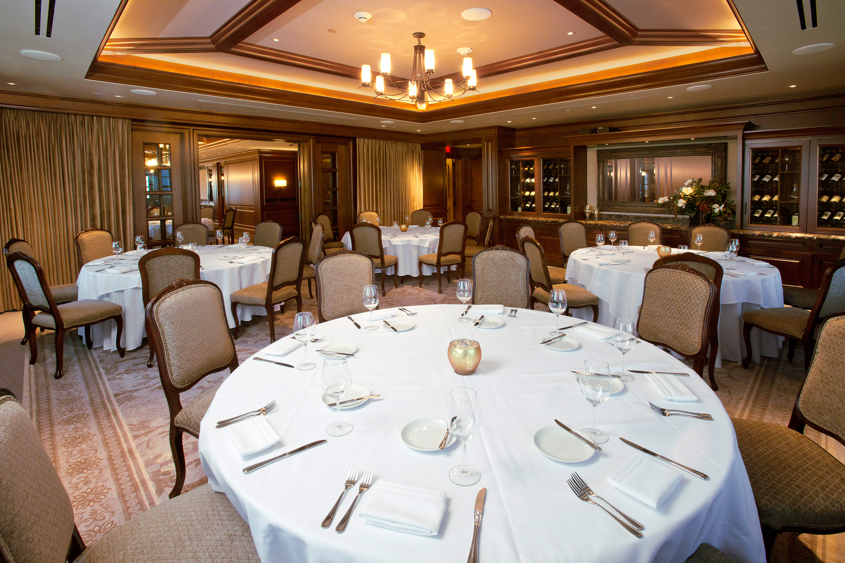 Comfortable room decorated in earth tones with dining tables, wine cabinets, bar, and AV presentation capabilities