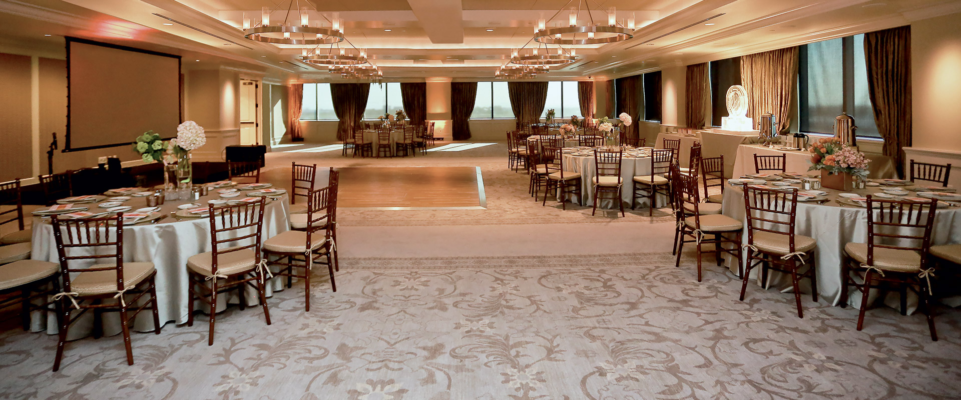 Elegant 6th floor room in cream, white, and burgundy, with dining tables, a dance floor, chandeliers, and oversized windows.