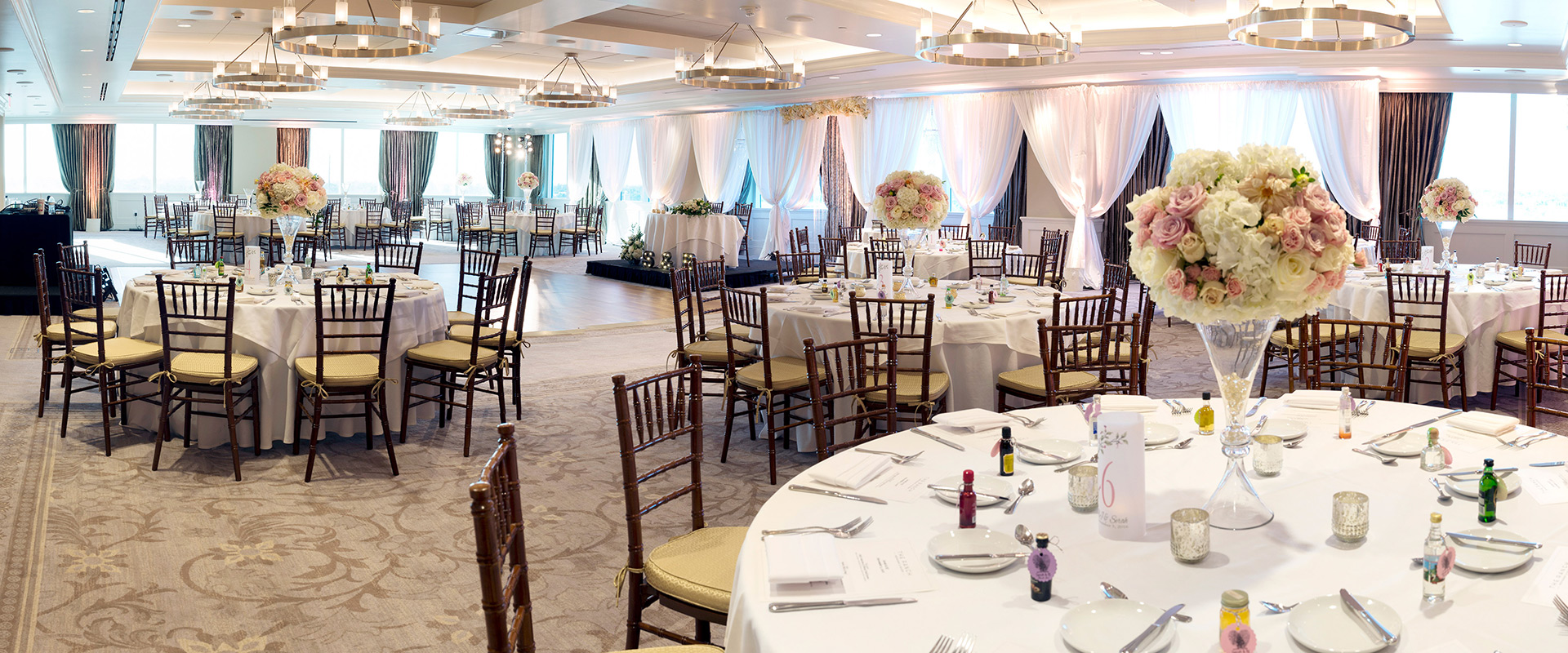 Large elegant room with tables and chairs and places settings for a wedding reception