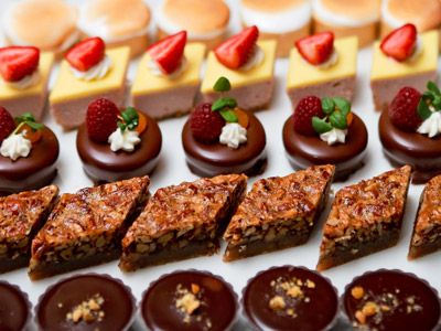 Rows of bite-sized strawberry-topped cakes, chocolate-coated donuts, rich brownies, and muffin tops on a white platter.