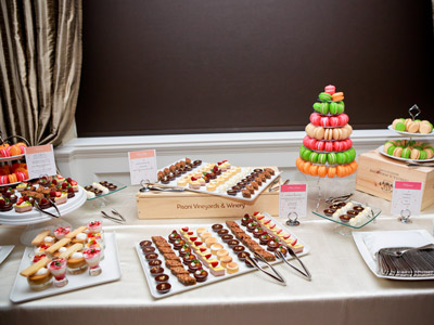 Table filled with an assortment of sweet treats, including candies, pastries, and a colorful Buche de Noel.