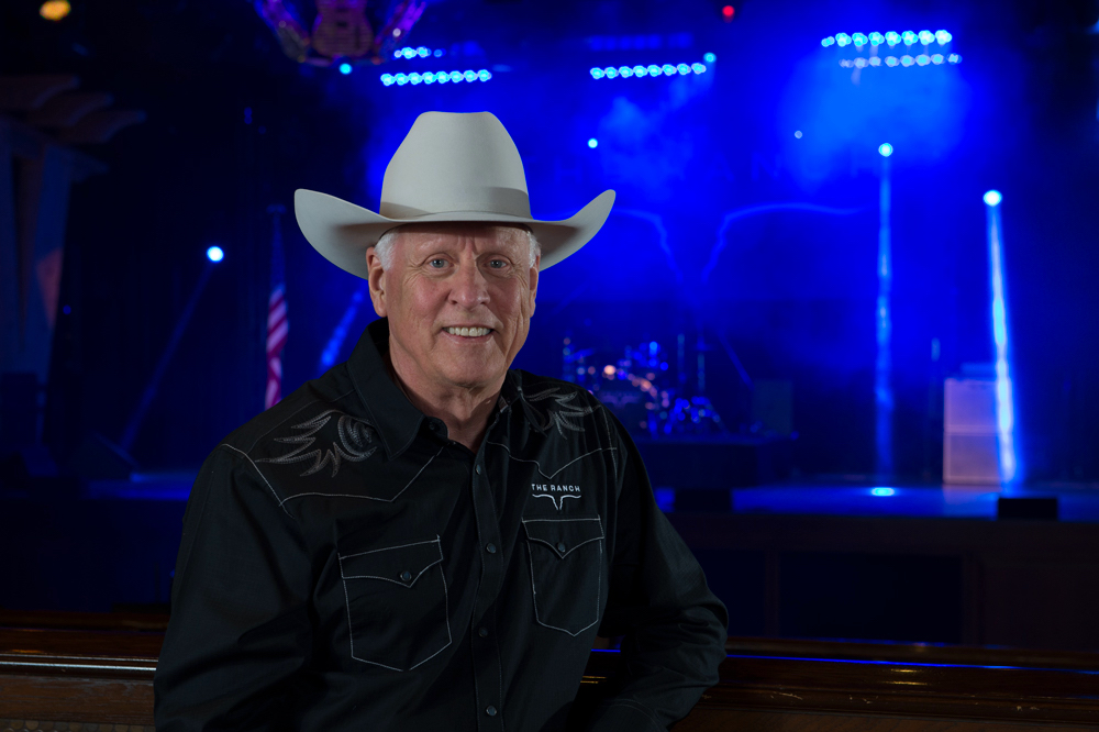 Andrew Edwards, in his white cowboy hat and black western shirt standing in front of the blue-lit stage.