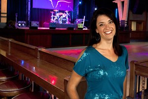Line dance instructor and choreographer, Kerry Kick, standing on the dance floor in front of The Saloon stage.