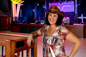 Country dancing instructor and choreographer, Shelly, in her cowgirl hat standing in front of The Saloon stage.