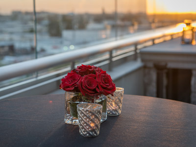 Closeup of a beautiful red flower and votive candles on The Terrace with Anaheim skyline in the background.