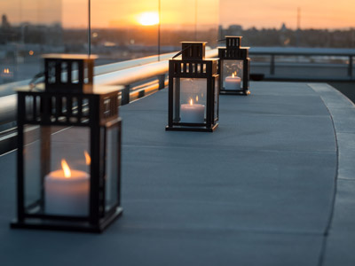 Closeup of three lanterns on The Terrace with the sun setting on the horizon.